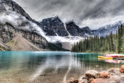 Moraine Lake with clouds descending on the Valley of the Ten Peaks in the background and some canoes on the lake. HDR rendering.