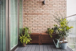 Morden residential balcony garden with bricks wall, wooden bench and plants.