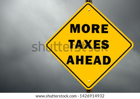 More taxes ahead conceptual road sign against stormy sky