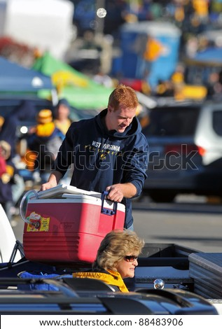 "MORGANTOWN, WV - NOVEMBER 5: A West Virginia University fan unloads a cooler from his truck as he ""tailgates"" prior to the football game between WVU and Louisville November 5, 2011 in Morgantown, WV"