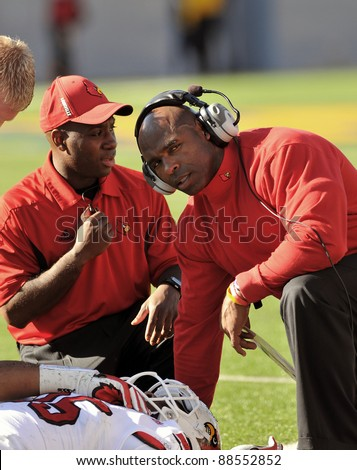 MORGANTOWN, WV - NOVEMBER 5: Louisville head coach Charlie Strong (r) checks on one of his injured players during the football game between Louisville and WVU November 5, 2011 in Morgantown, WV.