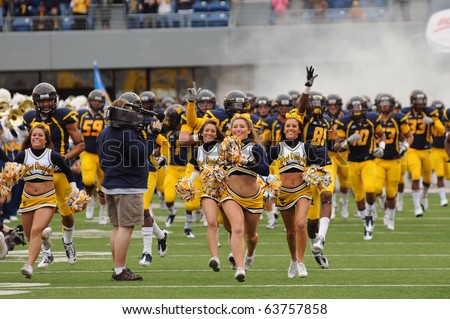 MORGANTOWN, WV - OCTOBER 23: Members of the WVU cheerleaders lead their football team onto the field prior to the game against Syracuse October 23, 2010 in Morgantown, WV.