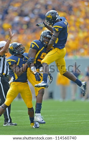 MORGANTOWN, WV - SEPTEMBER 29: West Virginia Mountaineers safety K.J. Dillon (air) celebrates a big play with a teammate during a Big 12 conference football game September 29, 2012 in Morgantown, WV.