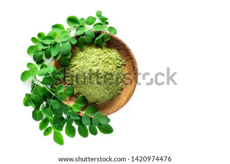 Moringa powder (Moringa Oleifera) in wooden bowl with original fresh Moringa leaves isolated on white background. Healthy product, superfood, vitamin. Top view.