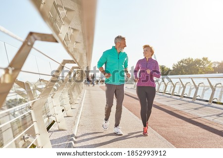 Morning activity. Full length shot of active mature family couple in sportswear smiling at each other while jogging together on a sunny morning. Joyful senior couple working out outdoors Foto stock ©