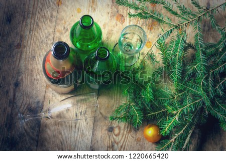 Morning after the celebration of the New Year. Several empty bottles of alcohol, fir branches, glasses on the dirty floor. Alcoholism, alcoholism and abuse concept #1220665420
