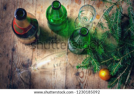 Morning after the celebration of the New Year. Several empty bottles of alcohol, fir branches, glasses on the dirty floor. Alcoholism, alcoholism and abuse concept #1230185092