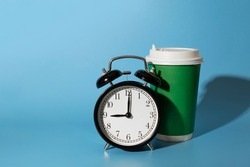 Morning alarm clock and disposable bright positive green paper cup or mug with shadow. Bright positive blue background with empty copy space for text. Deadline or pause concept. Take away beverage