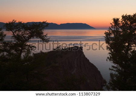 Morning at the cape Khoboy, Olkhon island, Baikal. Red, purple, and yellow sky, coast sunset with silhouette mountains and trees