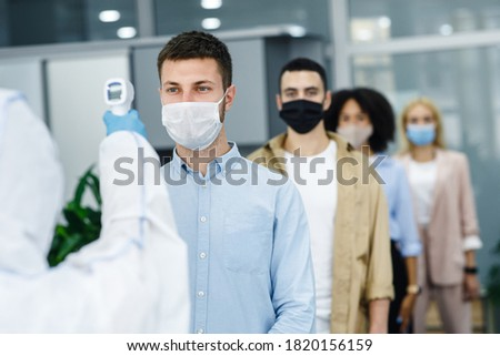 Morning at work during covid-19 epidemic. Person with contactless thermometer measures temperature of multiracial employees in protective masks an entrance of modern office, copy space