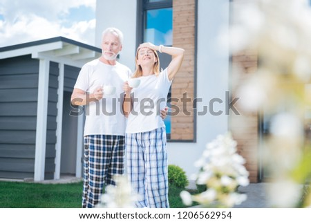Morning atmosphere. Blonde-haired beaming wife enjoying perfect morning atmosphere with her handsome husband