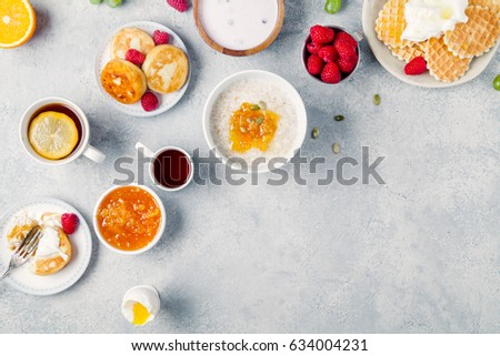 Morning atmosphere. Healthy breakfast with porridge, oatmeal, pancakes, lots of berries and snacks on blue rustic background. Copy space #634004231