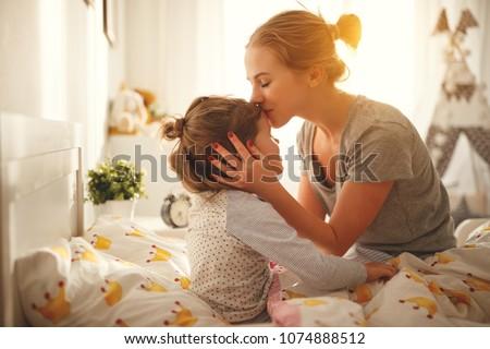 morning awakening. mother wakes her daughter in bed in morning #1074888512