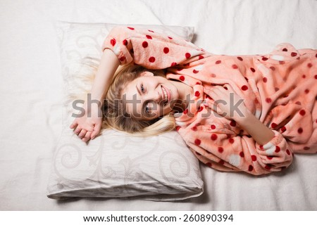morning beautiful girl woke up in bed smiling happy. beautiful blonde woke up in bed, stretching