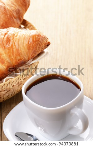 Morning black coffee with croissants on the wooden table