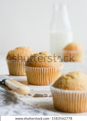 Morning breakfast vanilla muffins in white paper cups on white wooden cutting board with the bottle of fresh milk , white background, coseup view Photo stock ©