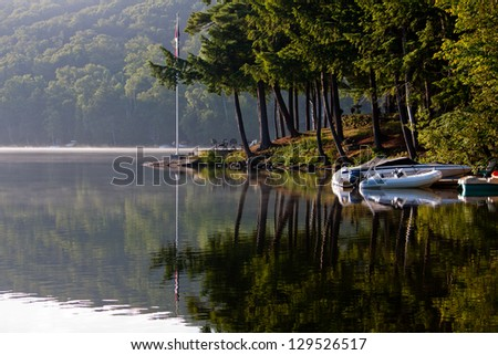 Morning breaks over the glassy still lake, looking out at boats docked and Muskoka pine trees