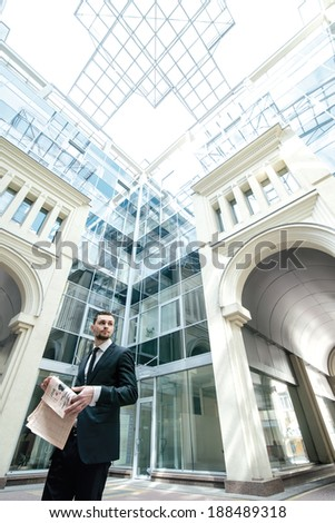 Morning business news. Business man formal wear goes to work in the business center and keeps reading the newspaper. Wide angel view from the down floor.