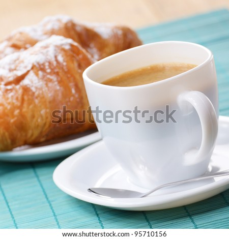 Morning cappuccino coffee with croissant on the wooden table