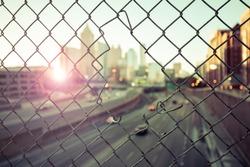 Morning city skyline through the wire mesh fence. Sunrise cityscape background
