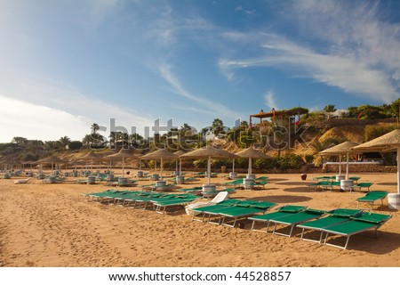 Morning Coastline with plank beds and umrellas in Egypt Sharm el-sheikh hotel