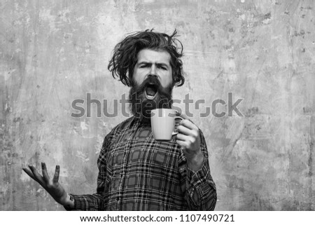Morning coffe. singing bearded man, caucasian hipster, with long beard and moustache pulling stylish fringe hair, haircut, in red plaid shirt with blue cup on abstract pink wall background