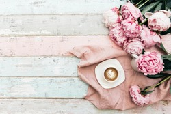 Morning coffee cup concept. Pink peony bouquet on vintage background. Top view, copy space