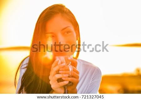 Morning coffee happy woman drinking hot drink enjoying first cup of the day on outdoor balcony in sunrise sunshine glow. Asian girl home comfort lifestyle.