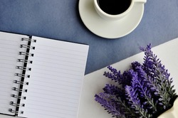 Morning coffee mug, empty notebook and purple lavender flowers on purple and white table, cozy summer breakfast, top view, flat lay