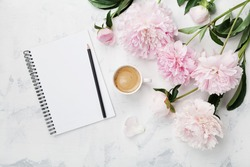 Morning coffee mug for breakfast, empty notebook, pencil and pink peony flowers on white stone table top view in flat lay style. Woman working desk.