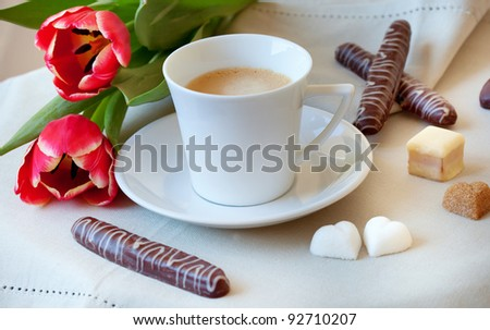 Morning coffee with cookies, heart-shaped pieces of sugar and flowers