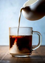 Morning coffee with cream. Pouring cream from white creamer into hot coffee in a glass cup on a wooden table.
