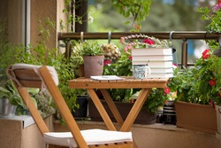 Morning coffee with relaxation on the balcony. Beautiful city terrace with many pots and vintage accessories.