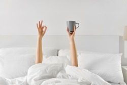 morning, comfort and people concept - young woman with cup of coffee lying in bed and showing ok hand sign at home bedroom
