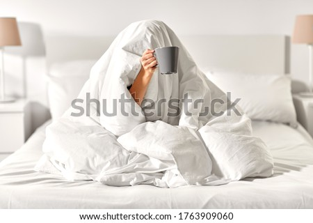 morning, comfort and people concept - young woman with cup of coffee sitting in bed under blanket at home bedroom