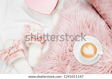 Morning concept. A cup of coffee on a pink pillow, slippers on the bed. Flat lay, top view