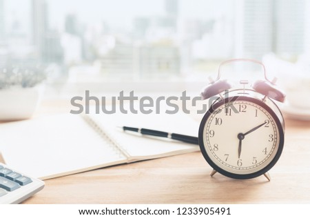Morning concept. The table clock has a nice day with a cup of coffee and a newspaper flower pot, located near the window in a luxury apartment with city views in the morning. #1233905491