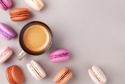 Morning cup of coffee and colorful cake macaron or macaroon top view. Flat lay.