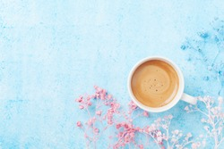 Morning cup of coffee and colorful flowers on blue pastel table top view. Flat lay style. Creative breakfast for Woman day.