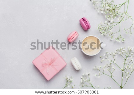 Morning cup of coffee, cake macaron, gift or present box and flower on light table from above. Beautiful breakfast. Flat lay style.