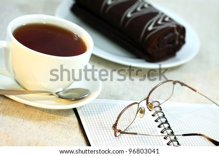 Morning cup of tea on a table with the chocolate roll, the opened daily log and points carelessly put from above