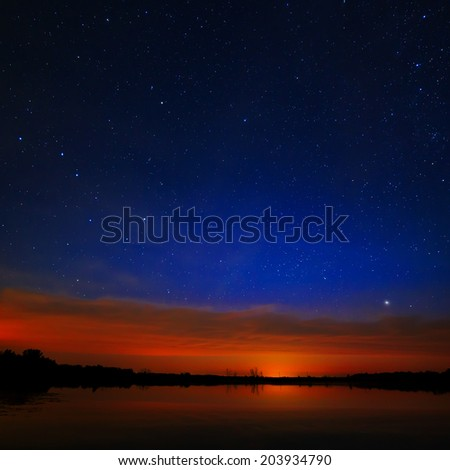 Morning dawn on a starry background sky reflected in the water of the lake. #203934790