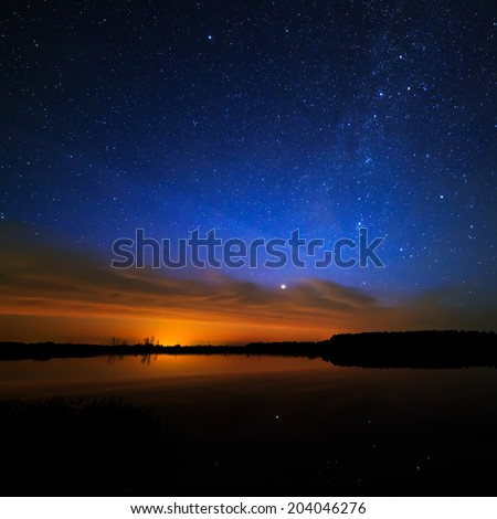 Morning dawn on a starry background sky reflected in the water of the lake. #204046276
