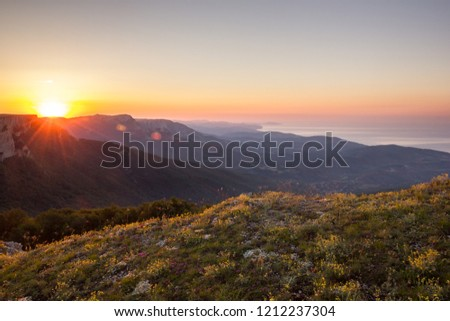 Morning Dawn Sunlight of Bright Golden Sunrise with Yellow Flowers Green Hills and Colorful Sky Summer Landscape