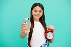 morning. drinking per day. be hydrated. kid hold glass and clock. child feel thirsty. teen girl alarm clock. healthy childhood. time to drink water. water balance in body. hydration vitality.