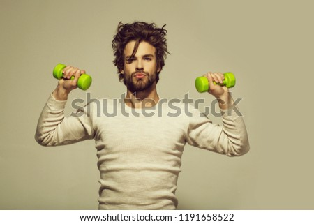 morning exercise of man with barbell or dumbbell workout, has disheveled and uncombed long hair and beard on face in white underwear on grey background, morning exercise and wake up, barbershop, sport
