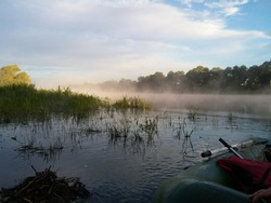 Morning fishing in Belarus on the Pripyat River. The first rays of the summer sun, dawn, fog to fall into the water. Fishing on an inflatable boat with a motor. Wild Belarusian nature. Before sailing.