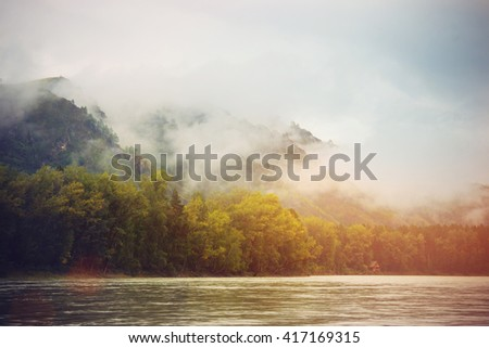 Morning fog and clouds on mountain tops near the river. Beautiful Altai Landscape #417169315