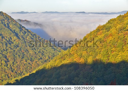 Morning fog at sunrise in autumn mountains of West Virginia in Babcock State Park