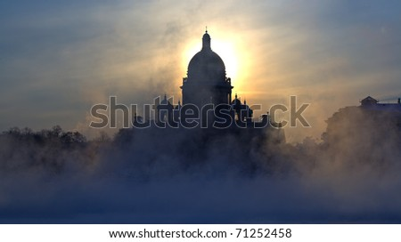 Morning fog during strong frosts on quay of the river of Neva and St. Isaac's Cathedral in Saint-Petersburg on the sky background.